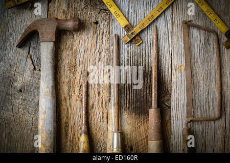 Marteau, tournevis, scie à main et ruban de mesure sur fond de bois rustique Banque D'Images