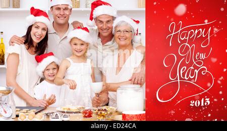 Image composite de cuisson enfants gâteaux de Noël dans la cuisine avec leur famille Banque D'Images