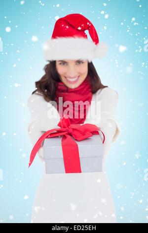 Image composite de brunette de fête à santa hat giving gift