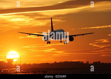 Un avion à l'atterrissage à un aéroport pendant le coucher du soleil en vacances durant un voyage Banque D'Images