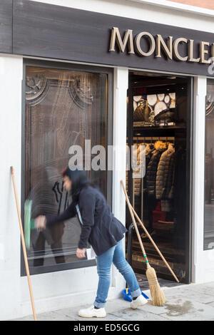 Jeune femme lave-vitre de magasin de vêtements Moncler, Venise, Italie Banque D'Images