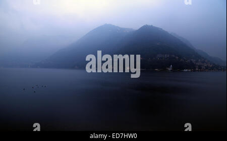 Un lac sombre avec deux montagnes surplombant elle est plongée dans le brouillard. Banque D'Images