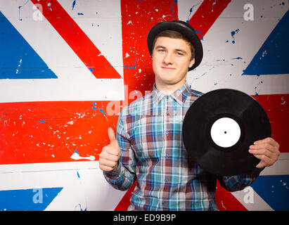 Close up Smiling Young Man in Tee shirt manches longues à carreaux et Hat Holding Vinyl Record Showing Thumbs Up Banque D'Images
