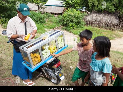 Voyages Moto vendeur sur route dans un petit village, la vie locale, près de Bagan, Myanmar Banque D'Images