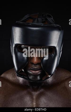 Close-up portrait of strong African man wearing head protector sur fond noir. Tough male boxer en boxe casque. Banque D'Images