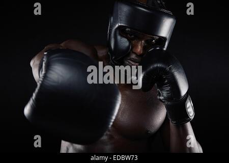 Portrait d'homme africain pratiquer la boxe à la caméra à contre fond noir. Male boxer de jeter un coup à l'avant. Banque D'Images