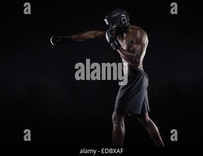 Vue de côté de l'homme musclé boxe sur fond noir. Young African American male boxer pratiquer la boxe de l'ombre. Banque D'Images