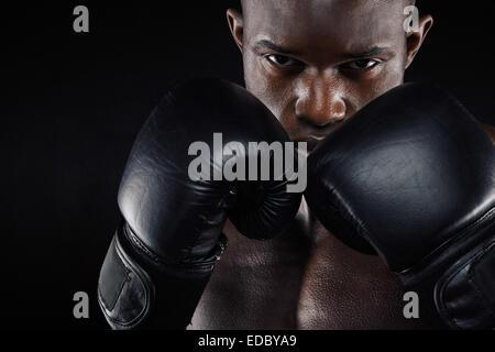 Portrait d'un jeune male boxer dans une position de combat sur fond noir. Jeune homme faisant l'exercice de boxe.