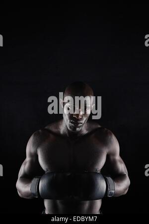 Portrait of professional male boxer contre l'arrière-plan noir. Fort et musclé young man in boxing gear. Banque D'Images
