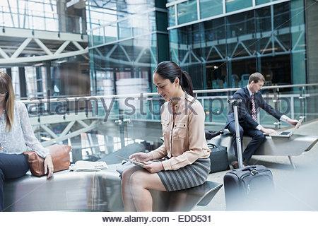 Les gens d'affaires à l'aide de la technologie dans l'atrium de l'aéroport Banque D'Images