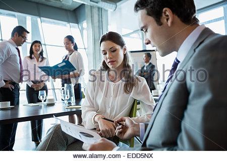 Les gens d'affaires l'examen des données dans la salle de conférence réunion Banque D'Images