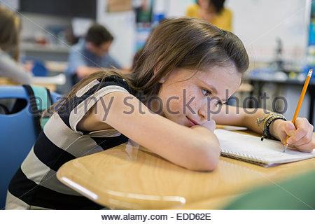 Élève d'école élémentaire écrit at desk in classroom Banque D'Images