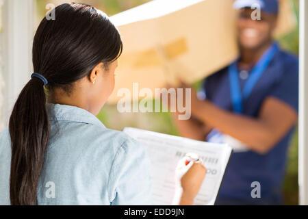 Vue arrière femme africaine signature recevant de courier guy Banque D'Images