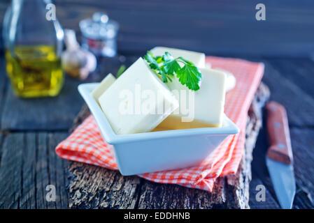 Le fromage dans le bol et sur une table Banque D'Images