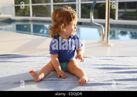 Baby Girl sitting on une serviette devant piscine Banque D'Images