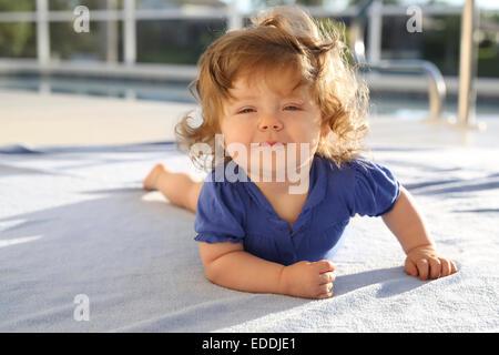 Portrait of baby girl allongé sur une serviette devant piscine Banque D'Images