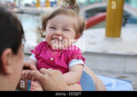 Portrait of laughing baby girl sitting on mother's lap Banque D'Images