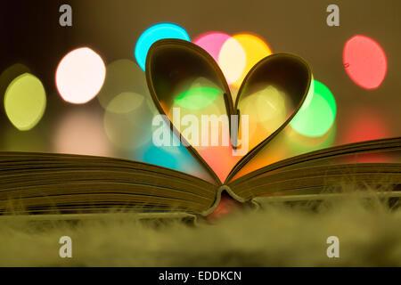 Les pages d'un livre en forme de coeur en face de lumières colorées Banque D'Images