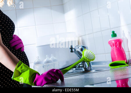 Une femme lave et prépare ses bouteilles de lait pour avoir exprimé dans la semaine 30 de la grossesse. Banque D'Images