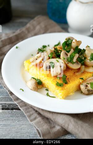 Polenta avec champignons savoureux dans une assiette blanche, de l'alimentation close up
