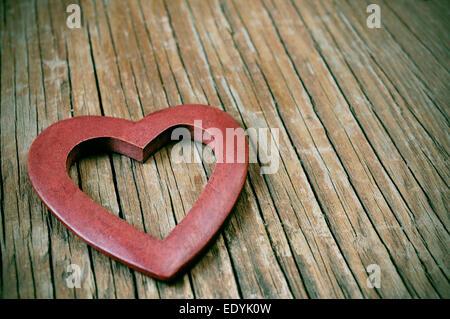 Un coeur en bois sur une surface en bois rustique avec un effet de filtre Banque D'Images