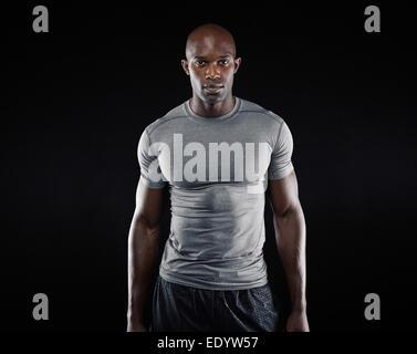 Portrait de jeune homme fit construire musculaire avec l'article sur fond noir. L'afro-américain modèle de remise en forme.