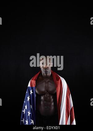 Portrait d'homme musclé enveloppé dans le drapeau américain sur fond noir. Athlète africain avec drapeau du pays. Banque D'Images