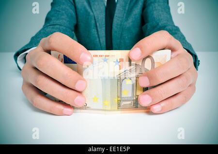 Man in suit dans un bureau avec une liasse de billets en euros dans ses mains Banque D'Images