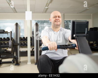 Homme mature prend soin de sa santé et il l'aviron dans la salle de sport Banque D'Images