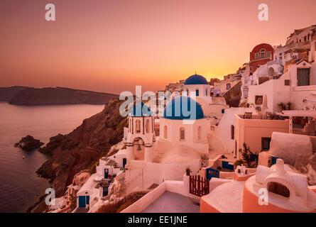 Eglise grecque avec trois coupoles bleues au coucher du soleil, Oia, Santorin (thira), îles Cyclades, îles grecques, Banque D'Images