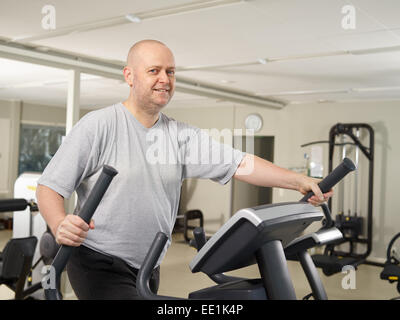 Homme mature prend soin de sa santé et il a utiliser dans la salle de fitness elliptiques d'entraîneur Banque D'Images
