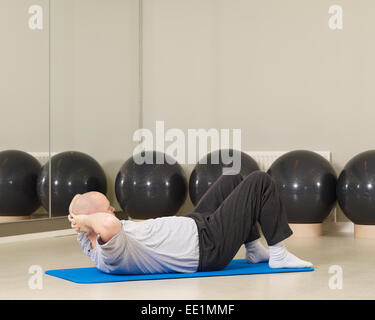 Homme mature prend soin de sa santé, il s'étend dans l'exercice de pilates et d''une salle de sport Banque D'Images