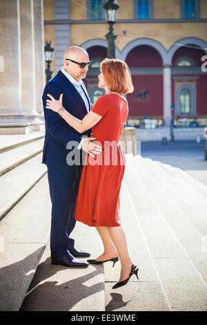 Senior couple embrasse sur l'extérieur, escalier, Munich, Bavière, Allemagne Banque D'Images
