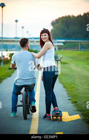 Jeune couple avec vélo BMX et skateboard en plein air