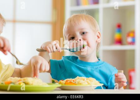 Kid boy eating spaghetti dans pépinière Banque D'Images