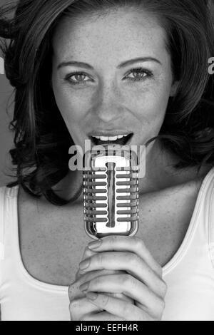 Chanteuse rousse rétro avec microphone chantant son cœur.
