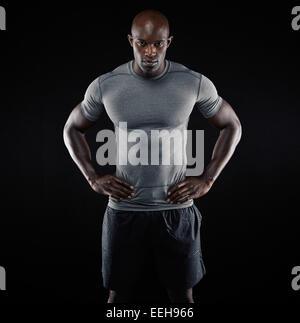 Portrait of muscular young man in sportswear debout avec ses mains sur les hanches à l'arrière-plan noir. L'Afrique Banque D'Images
