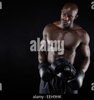 Portrait de jeune homme sportif avec casque de boxe holding corps musculaire. African Male boxer sur fond noir Banque D'Images