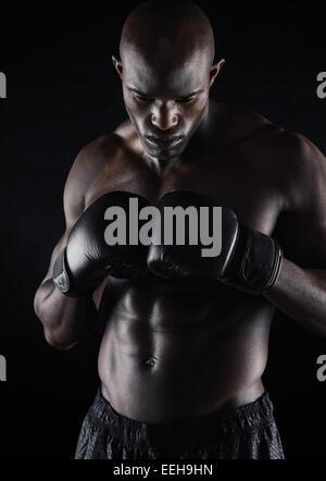 Fit young man wearing boxing gloves sur fond noir. Boxeur professionnel se préparer à combattre. Banque D'Images