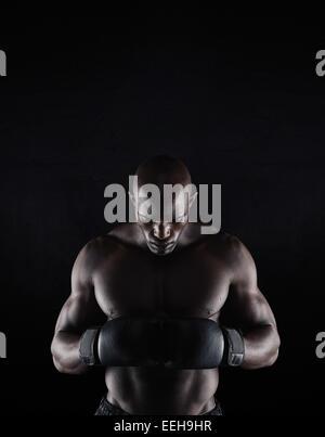 Portrait de jeunes professionnels male boxer sur fond noir. La préparation pour l'Afrique. lutte boxer Banque D'Images