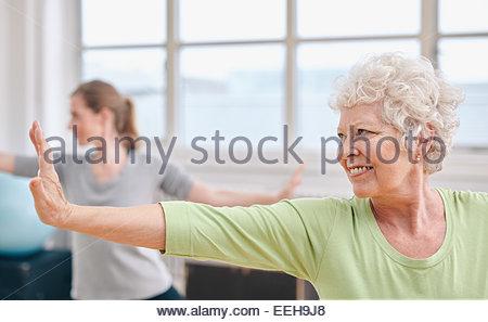 Portrait of senior woman practicing yoga au cours de gymnastique. Femme âgée s'étendant ses bras . Banque D'Images