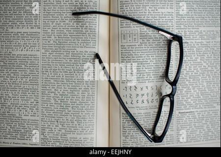 Paire de lunettes de lecture reposant sur une encyclopédie ouverte