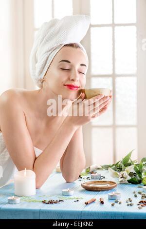 Souriante jeune femme avec une tasse de tisane dans serviette de bain salon de coiffure. Traitement à base de plantes. Banque D'Images