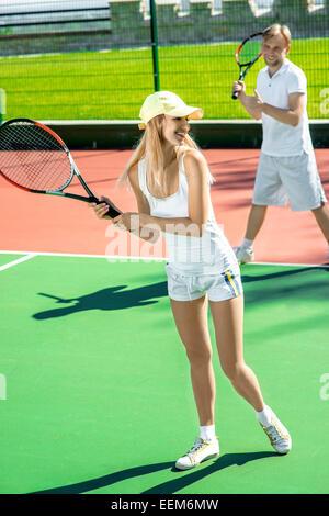 Deux jeunes mariés à jouer au tennis en blanc sportwear sur le court de tennis en extérieur dans l'été Banque D'Images