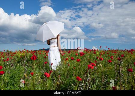 Femme avec parapluie blanc debout dans le champ de coquelicots rouge Banque D'Images