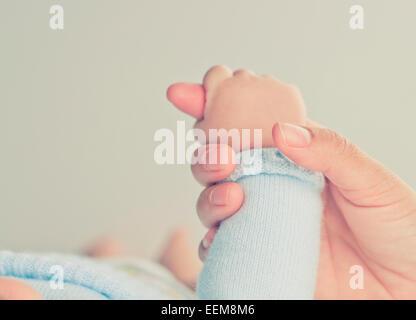 Gros plan de la main d'une mère tenant la main d'un bébé garçon Banque D'Images
