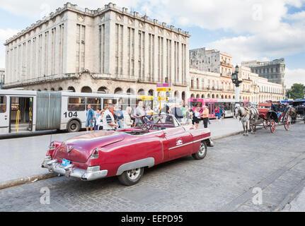 American Vintage Classic marron élégante voiture décapotable fonctionnant comme un taxi garé dans dans une rue de la Vieille Havane, Cuba en face d'un cheval et un chariot