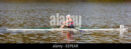 Un homme sur un crâne d'aviron sur une rivière. Banque D'Images