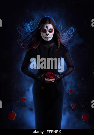 Femme en robe noire avec crâne en sucre makeup holding red rose avec pétales tombent au fond sombre Banque D'Images