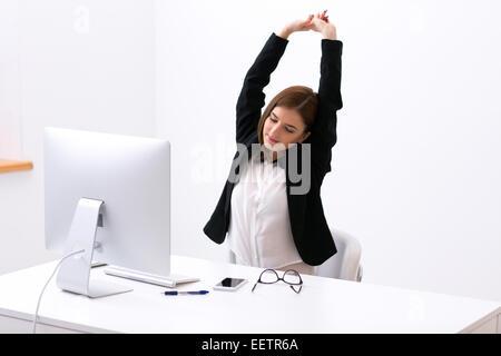 Businesswoman assis à la table dans le bureau et s'étend ses mains au-dessus de la tête Banque D'Images